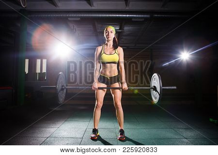Theme Of Bodybuilding And Training For A Beautiful Body, Crossfit. A Strong Girl Does An Exercise Wi