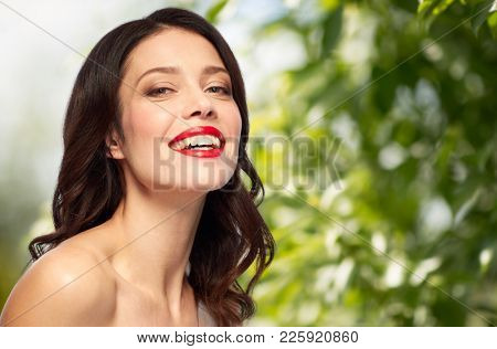 beauty, organic, make up and people concept - happy smiling young woman with red lipstick over green natural background