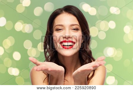 beauty, make up and people concept - happy smiling young woman with red lipstick holding something imaginary on palms over summer green lights background