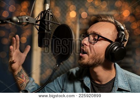 music, show business, people and voice concept - male singer with headphones and microphone singing song at sound recording studio over festive lights