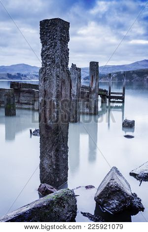 Old Concrete Jetty Posts Revealed At Low Water, With Very Smooth Water, In Moody Light.