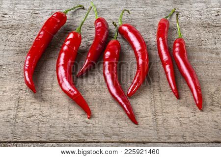 Red Chillies On Rustic Background - Seven Red Chillies On A Plank Or Rustic Background.