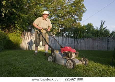 Older Man Mowing The Lawn With A Gas Lawnmower
