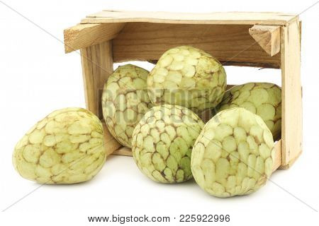 fresh cherimoya fruits (Annona cherimola) in a wooden crate on a white background