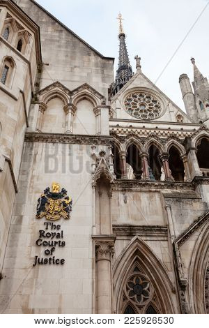 The Royal Courts of Justice (the Law Courts) Victorian Gothic exterior with sign and coat of arms, City of Westminster, Central Area of Greater London, UK