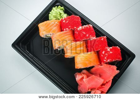Beautiful Rolls In Black Container On White Background With Reflection, For A Menu Or Website