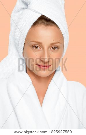 Beauty And Spa. Beautiful Woman With Perfect Fresh Skin Face In Towel On Her Head. Faded Pastel Back