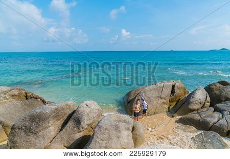 Siblings Brother And Sister Run And Play Amongst Large Rocks On Shore With Turquoise Sea Beyond On T