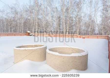 Concrete Rings In The Snow. The Rings For The Well Stand On The Snow In Winter.