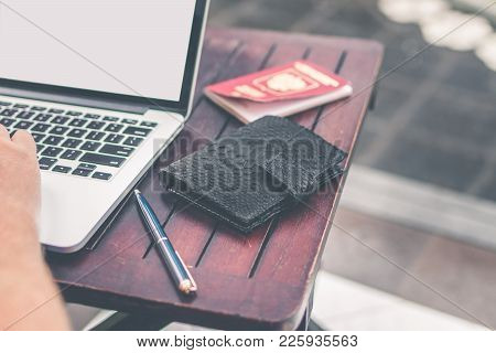 Man Doing Online Shopping With Credit Card, Laptop And Luxury Snakeskin Python Wallet.