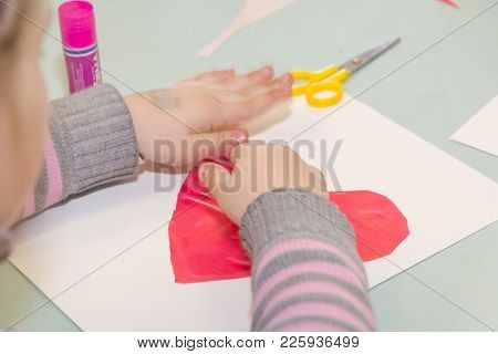 The Child Glues The Heart. The Child Is Engaged In Needlework.