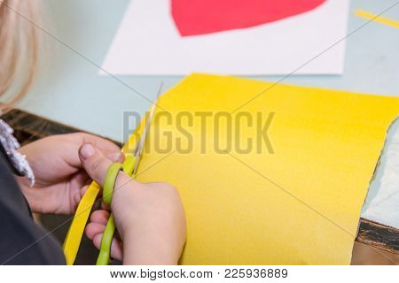 The Child Cuts Out Of Paper. The Child Is Engaged In Needlework.