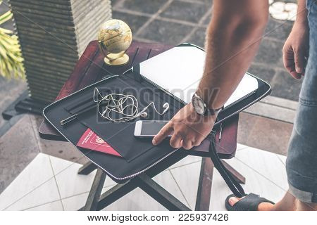 Man With Luxury Snakeskin Python Laptop Case On A Table Outside The Asian Garden. Men Fashion Concep