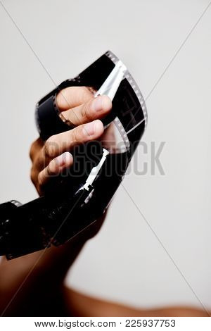 closeup of a young caucasian man with a filmstrip in his hand, against an off-white background