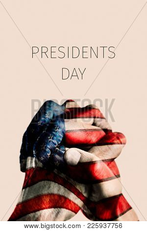 the clasped hands of a young man, patterned with the flag of the United States, and the text presidents day on a beige background