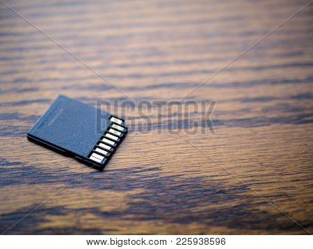 Sd Card Sitting On Wood Grain Desk.