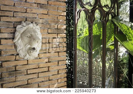 Statue Of Lion Head On Brick Wall, Stock Photo