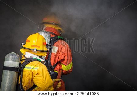 Two Firemen Water Spray By High Pressure Nozzle To Fire And Searching For Rescue In Dark Smoke With
