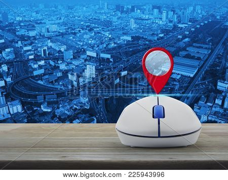Map Pin Location Button With Wireless Computer Mouse On Wooden Table Over City Tower, Street And Exp