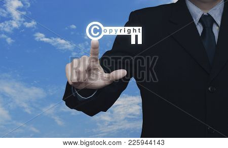 Businessman Pressing Copyright Key Icon Over Blue Sky With White Clouds, Copyright And Patents Conce