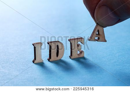 Idea From Wooden Letters On A Blue Background, A Man's Hand Holds A Letter A