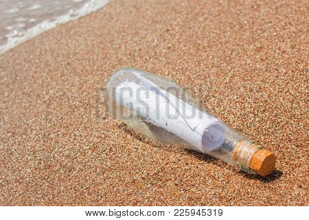 Paper Message In A Glass Bottle With A Cork On The Sand. In The Background, The Sea And Waves. A Not