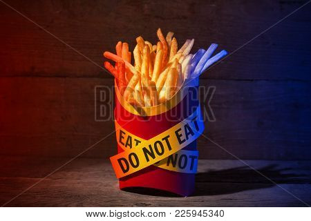 French Fries In A Red Packing Box On A Wooden Table With Yellow Police Ribbons With The Words Do Not