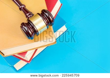 Judge's Wooden Hummer On Stack Of Law Books On A Blue Background. Top View.