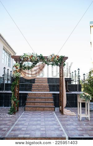 Rustic Wedding Arch. Wedding Arch Made Of Wooden Square Frame, Beige Cloth, White And Orange Flowers