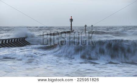 Beautiful Dramatic Stormy Landscape Image Of Waves Crashing Onto Beach At Sunrise