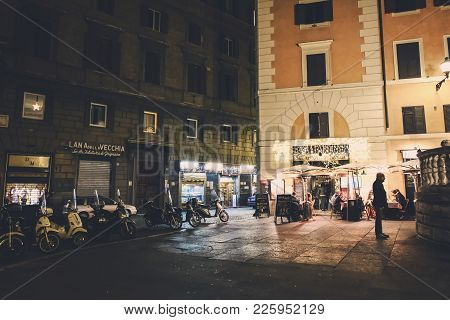 Rome, Italy - November 9 2017: Night Life In Rome. People At A Restaurant And Many Scooters Parked O