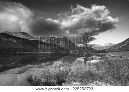Stunning  Black And White Sunrise Landscape Image In Winter Of Llyn Cwellyn In Snowdonia National Pa