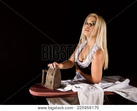 Sexy Blonde Woman In Housekeeper Suit, Ironing White Shirt With Old Iron. Retro Style. Housewife Con