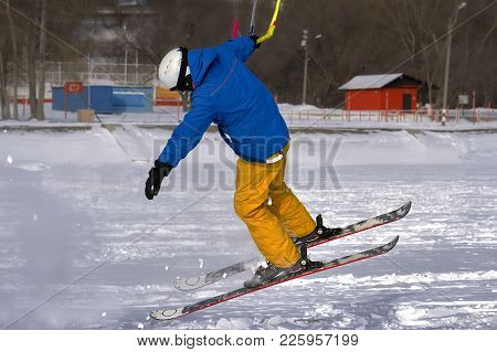 A Male Athlete Engaged In Snow Kiting On The Ice Of A Large Snowy Lake. He Performs The Jump. Winter
