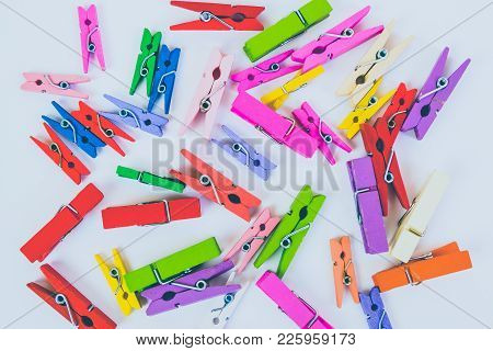 Pile Of Colorful Wooden Clothespins. Colored Clothes Peg On White Background.