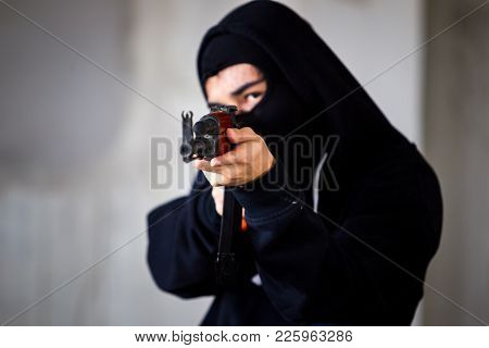 Unidentified Man In Black Suit With Face Masked Is Aiming Assault Rifle To The Target Close Up.