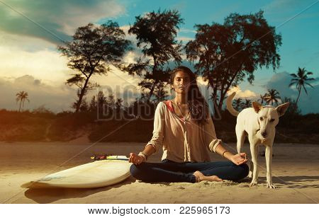Indian Surfer Girl Meditating In Lotus Pose On The Beach At Sunset Next To Surfboard And Dog Looking