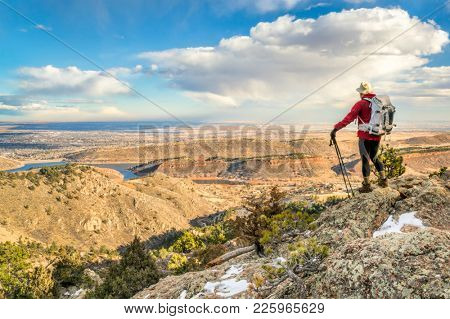 a backpacker on a mountain ridge overlooking Colorado foothills and plains - Horsetooth Rock trail above Fort Collins