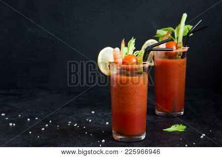 Bloody Mary Cocktail In Glasses With Garnishes. Tomato Bloody Mary Spicy Drink On Black Stone Backgr