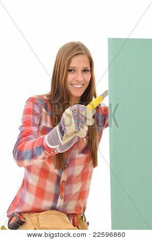 Woman cutting a green gypsum board
