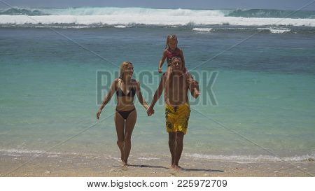 Happy Beautiful Family With Child Walking Together On Tropical Beach During Summer Vacation. Bali. F