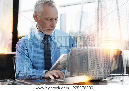 Busy Worker. Calm Attentive Smart Person Looking Concentrated While Sitting At The Table With A Mode