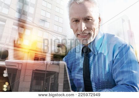 Cheerful Employer. Pleasant Optimistic Mature Man Being In A Good Mood And Smiling While Sitting Wit