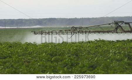 Aerial View Tractor Spraying The Chemicals On The Large Green Field. Spraying The Herbicides On The