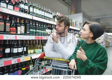 A Beautiful Young Couple Chooses Wine In The Alcohol Department Of The Supermarket. Family Shopping