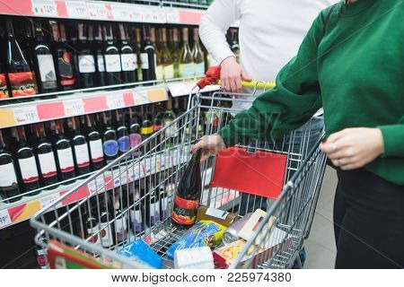 The Girl Puts A Bottle Of Wine In A Cart For Shopping In A Supermarket. A Young Couple Chose Alcohol