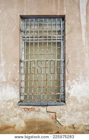 Abandoned Cracked Stucco Brick Wall With Window Grilles