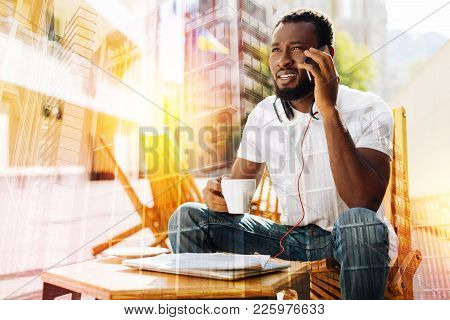 Phone Talk. Calm Attentive Young Man Sitting Alone With A Cup Of Coffee In His Hand And Slightly Fro