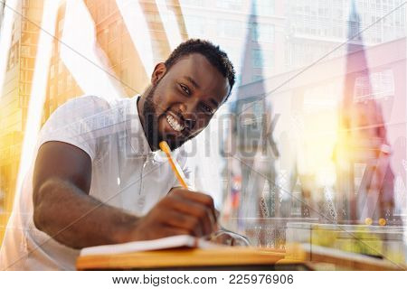 Excited Student. Emotional Cheerful Diligent Student Smiling And Writing An Interesting Report While