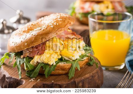 Healthy Freshly Baked Bagel Filled With Scrambled Eggs, Rucola And Fried Bacon. Served On Small Wood